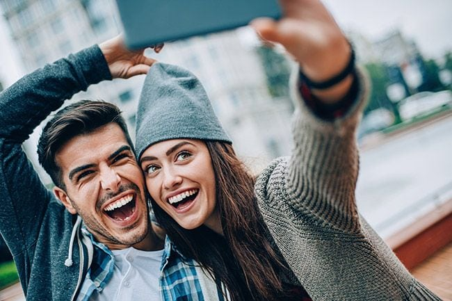 young couple taking a selfie together outside